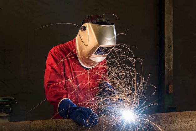 Trabajador soldadura tubería en un área de construcción
