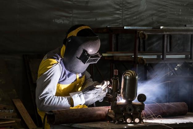 Trabajador soldando la pieza de acero por manual