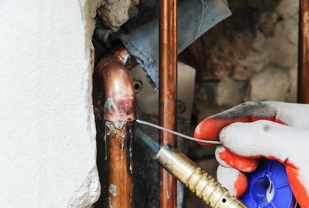 Un trabajador está soldando tuberías de cobre