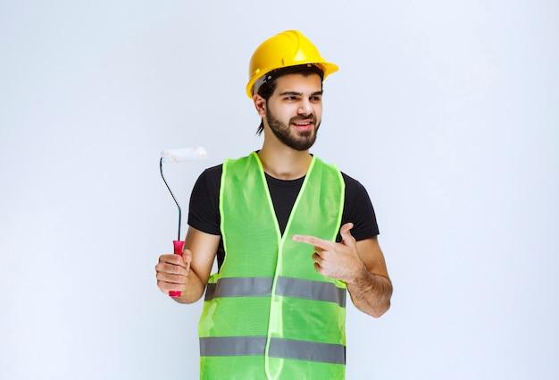 Trabajador sosteniendo un rodillo de acabado blanco para pintar paredes.