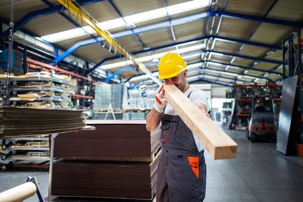 Trabajador sosteniendo tablones de madera y trabajando en fábrica de muebles o industria de procesamiento de madera