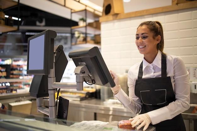 Trabajador de supermercado midiendo y vendiendo carne al cliente.