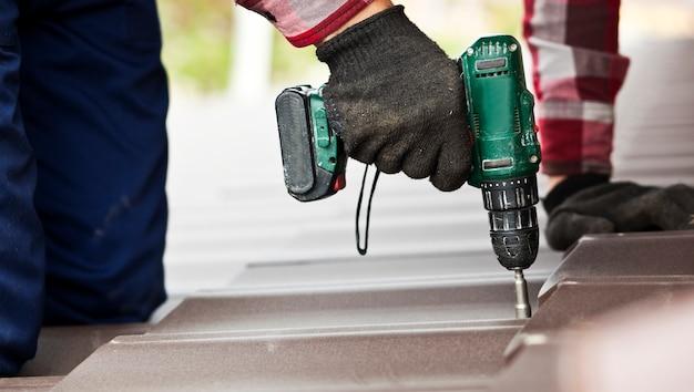 Trabajador techador atornillar teja metálica en el techo