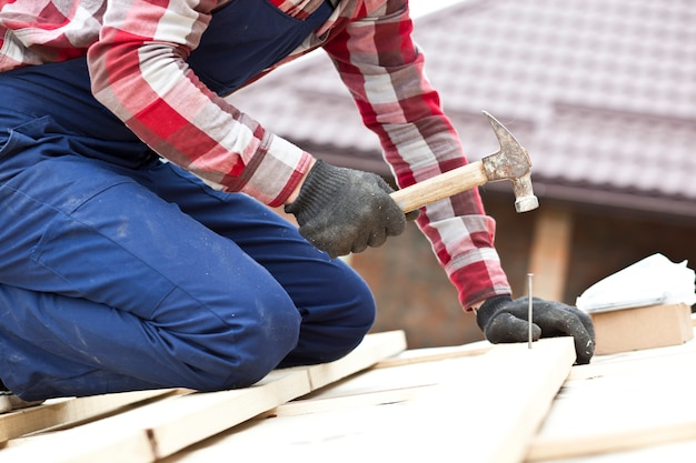 El trabajador del techador está martillando la uña en el tablón de madera.