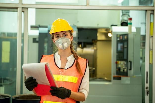 Trabajador técnico femenino trabajando y revisando la máquina en una gran fábrica industrial