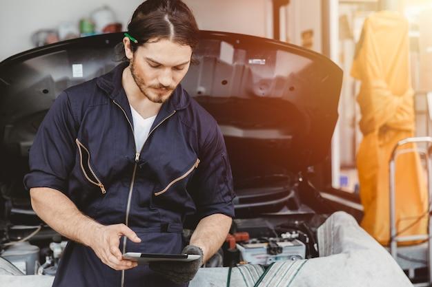 Trabajador de técnico de garaje que utiliza tecnología avanzada de tablet pc para comprobar el servicio y ajustar la ecu del coche en el centro de servicio de automóviles