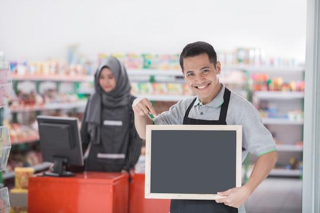 Trabajador de tienda masculina con pizarra en blanco