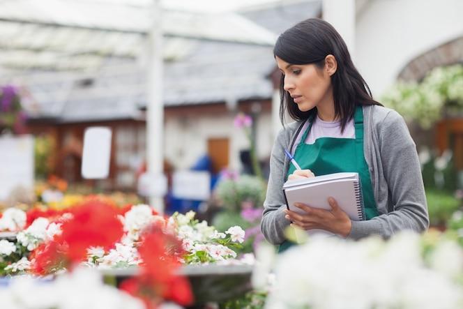 Trabajador tomando notas mientras selecciona una flor