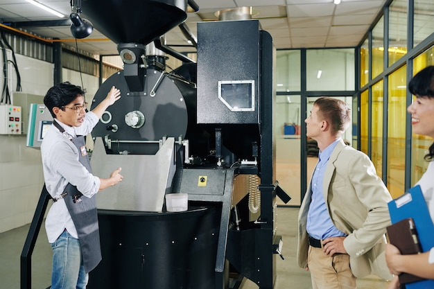 Trabajador tostador de café mostrando nueva máquina al inversor y hablando de sus beneficios