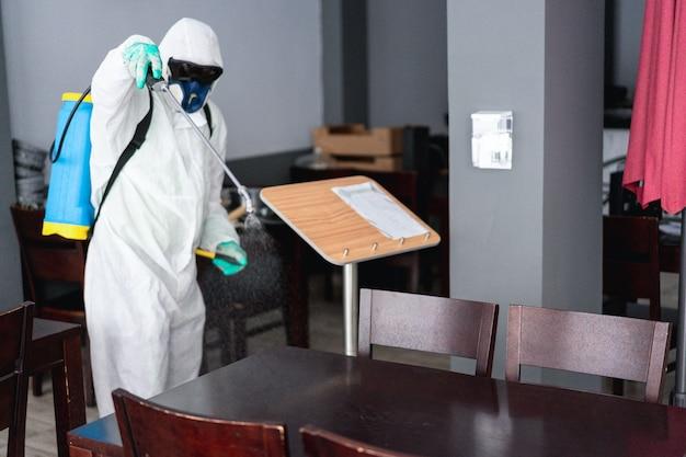 Trabajador en traje de materiales peligrosos con máscara de protección facial mientras realiza la desinfección dentro del bar restaurante - descontaminación de coronavirus para la atención médica de las personas