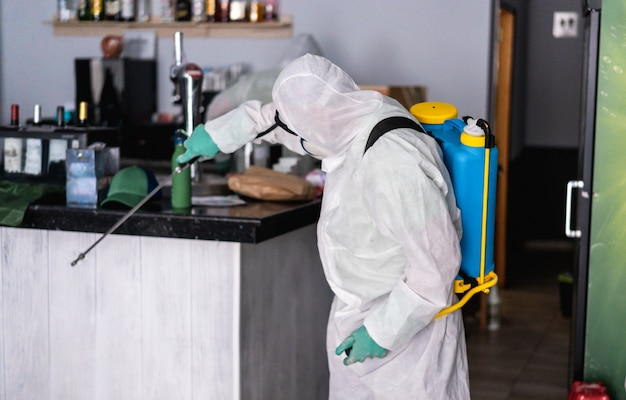 Trabajador en traje de materiales peligrosos con máscara de protección facial mientras realiza la desinfección dentro del bar restaurante