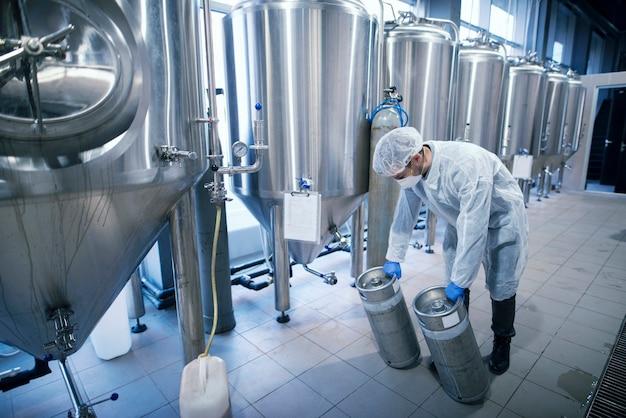 Trabajador en traje de protección que transporta productos químicos en depósitos metálicos