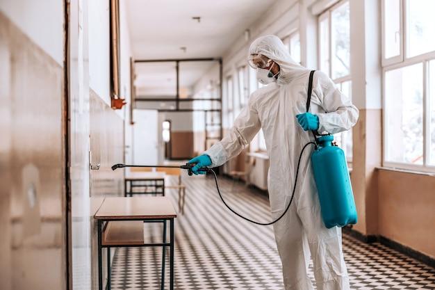 Trabajador en uniforme blanco estéril, con máscara y gafas sosteniendo rociador con desinfectante y puerta de rociado en el pasillo de la escuela.