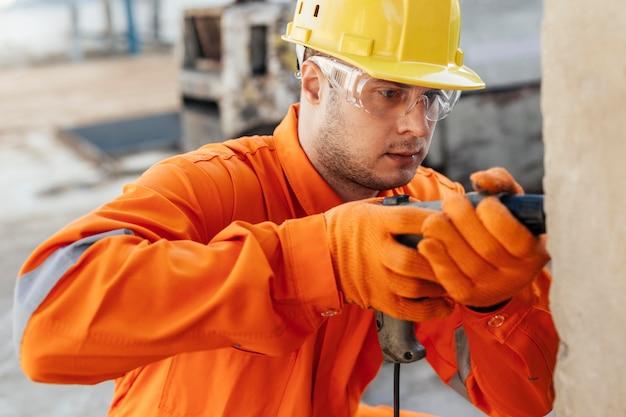 Trabajador en uniforme con casco y taladro
