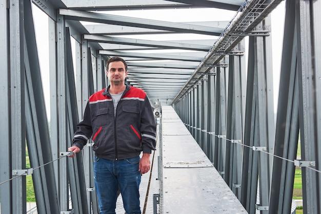Trabajador en uniforme contra el telón de fondo agri edificios