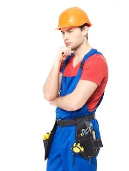 Trabajador en uniforme usando el casco pensando aislado en blanco