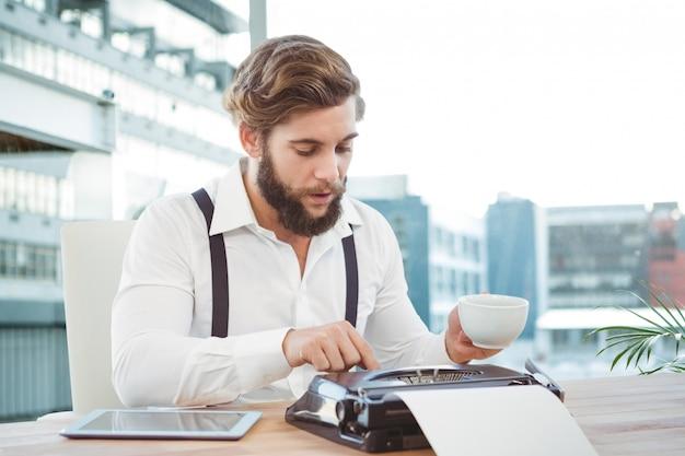Trabajador usando una máquina de escribir mientras toma un café