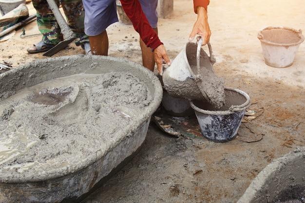 Trabajador verter hormigón de mezcla de cemento en bandeja