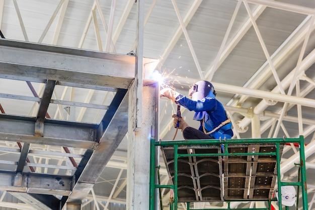 Trabajador en vidrios protectores de soldadura para la fijación de marcos de construcción de acero.