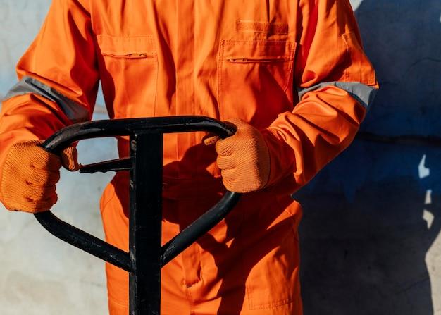 Trabajador de vista frontal en uniforme con guantes protectores manipulando carretilla elevadora