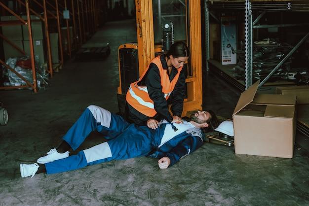Trabajadora de almacén proveyendo primeros auxilios al hombre