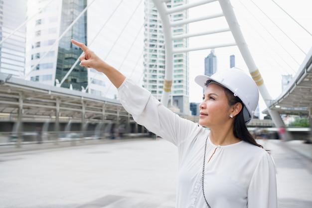 La trabajadora asiática que lleva un casco está de pie y apuntando hacia adelante.