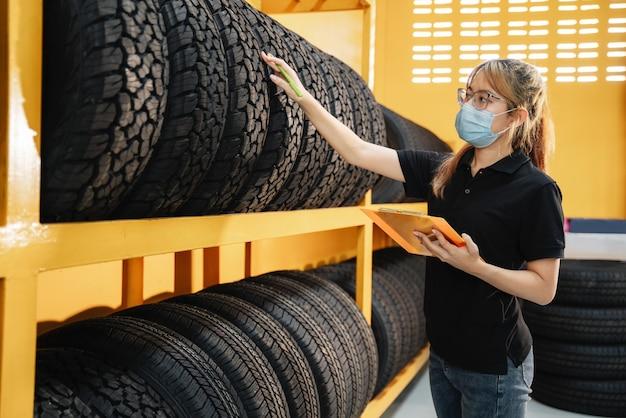 Trabajadora asiática usa una máscara para evitar la propagación del virus corona o covid-19, revisa el stock de neumáticos de automóvil en el almacén y escribe algunas notas.