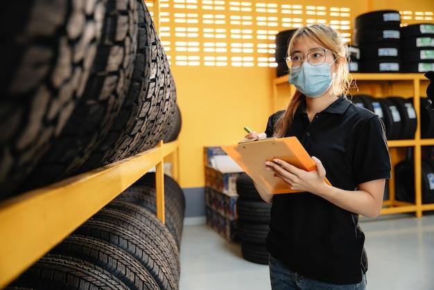 Una trabajadora asiática usa una máscara para evitar la propagación del virus corona o covid-19 está revisando el stock de neumáticos de automóvil en el almacén para la inspección de neumáticos para verificar el saldo del producto.
