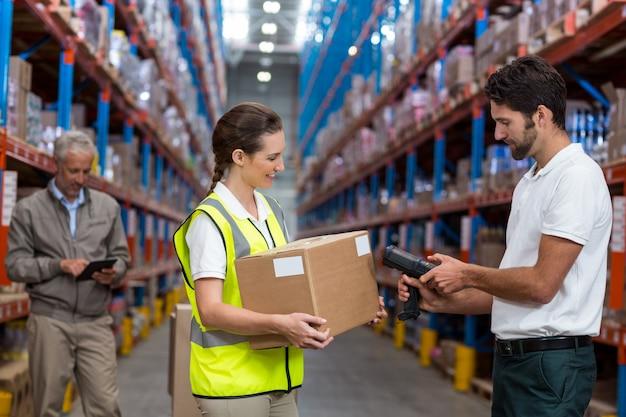 Trabajadora con caja de cartón mientras el trabajador de sexo masculino escaneando el código de barras