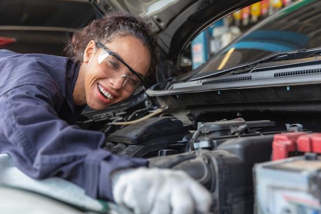 Trabajadora en el centro de servicio de automóviles, mujer en el trabajo mecánico de automóviles en el garaje servicio técnico de automóviles verificación y reparación del automóvil del cliente, inspección del automóvil debajo del capó cambio de aceite del motor de la batería