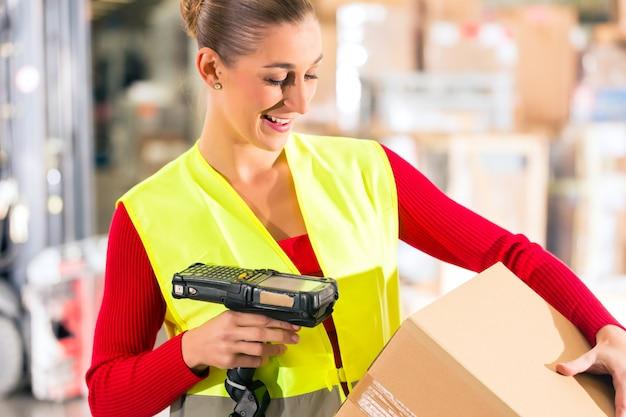 Trabajadora con chaleco protector y escáner, escanea el código de barras del paquete, de pie en el almacén de la empresa de transporte de carga