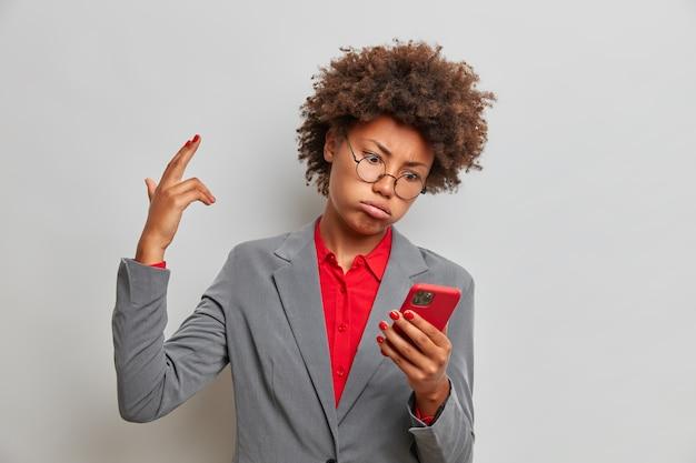 Trabajadora corporativa desesperada agotada y rizada hace pistola de dedo, está enferma y cansada de recibir mensajes de un extraño, sostiene un teléfono celular moderno, usa un traje de negocios