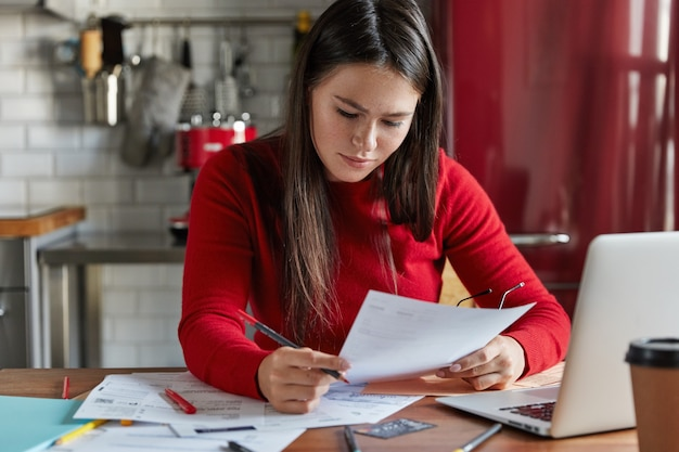 Trabajadora estudia análisis de mercado, hace pronósticos financieros, posa en el lugar de trabajo con documentación, dispositivo electrónico, trabaja en la cocina.