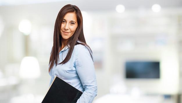 Trabajadora feliz con un cuaderno negro