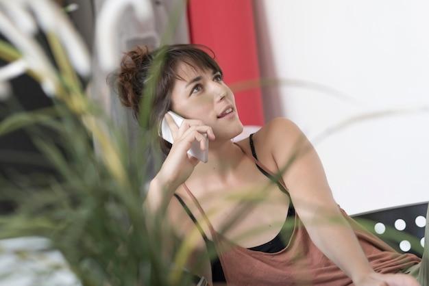 Trabajadora joven y bonita que usa un teléfono móvil.