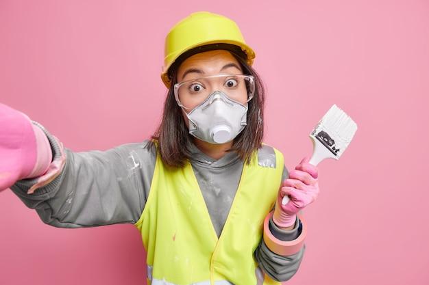 Trabajadora de mantenimiento sorprendida usa máscara protectora uniforme y gafas hace una foto de sí misma sostiene un pincel usa herramientas de construcción para reparar