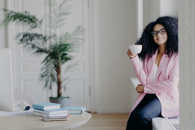 La trabajadora de negocios afroamericana positiva se sienta en el alféizar de la ventana, sostiene una taza de café