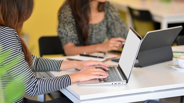 Trabajadora de negocios trabaja en una computadora portátil y una tableta digital en la sala de la oficina escribiendo en el teclado de la computadora portátil