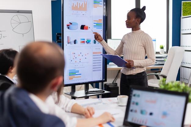 Trabajadora negra explicando las estadísticas de la empresa