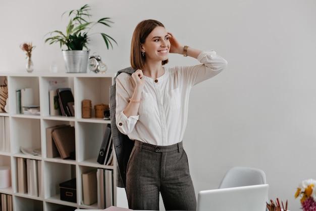 Trabajadora de oficina exitosa en pantalones grises y camisa ligera con poses de sonrisa de pie en el lugar de trabajo.
