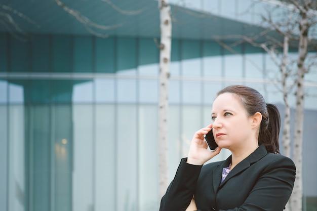 La trabajadora de la oficina está hablando por teléfono fuera de la oficina