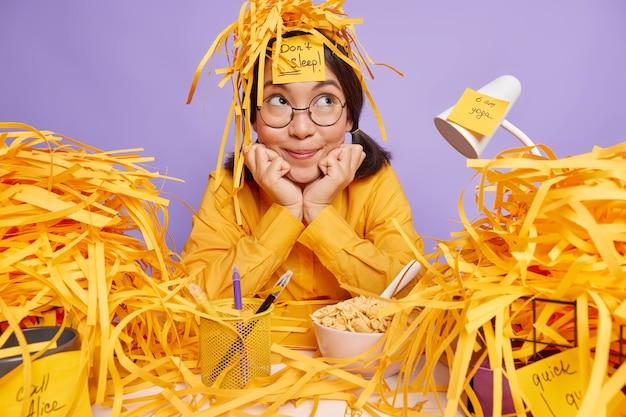 Trabajadora de oficina soñadora reflexiva con desperdicios de papel en la cabeza mantiene las manos debajo de la barbilla mira hacia otro lado pensativamente posa en el escritorio prepara el proyecto sobre fondo púrpura