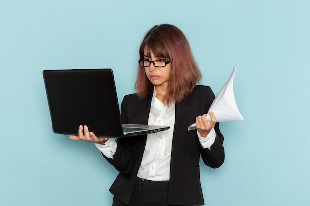Trabajadora de oficina vista frontal en traje estricto usando una computadora portátil y sosteniendo papeles sobre una superficie azul claro