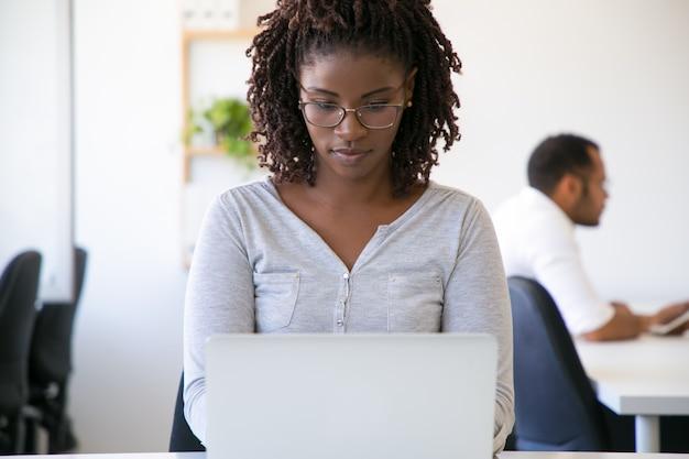 Trabajadora pensativa enfocada usando laptop