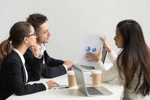 Trabajadora presentando plantillas visuales a compañeros de trabajo.