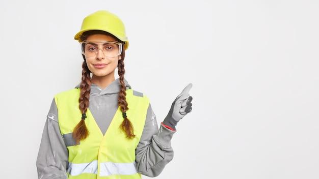 Trabajadora profesional ingeniera vestida con casco protector uniforme de trabajo, gafas transparentes y guantes indica en el espacio de la copia demuestra ideas para la construcción de edificios. ingenieria