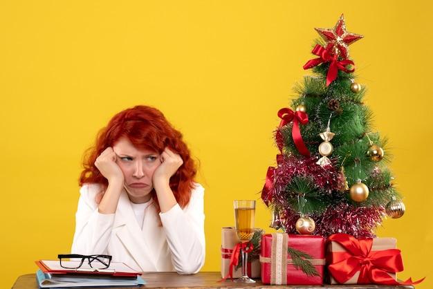Trabajadora sentada detrás de la mesa con regalos de navidad y árbol aburrido en amarillo