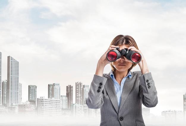 Trabajadora seria con traje gris usando los prismáticos