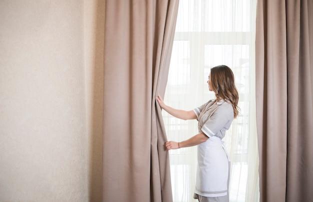 Trabajadora de servicio de camarera con cortinas de apertura de ventana en la habitación