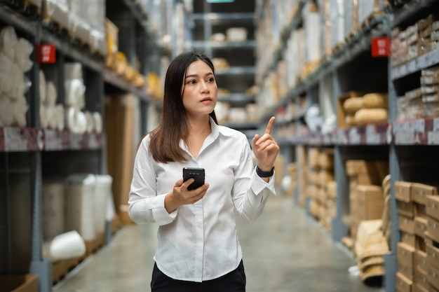 Trabajadora con smartphone para comprobar el inventario en la tienda del almacén